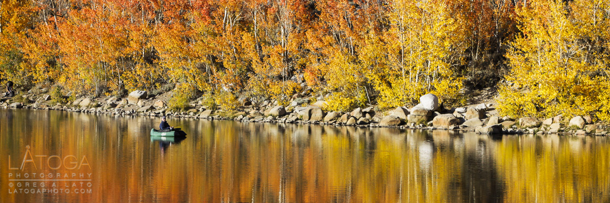 Panoramic of fisherman floating in North Lake  under colorful Autumn Aspen near Bishop, California.