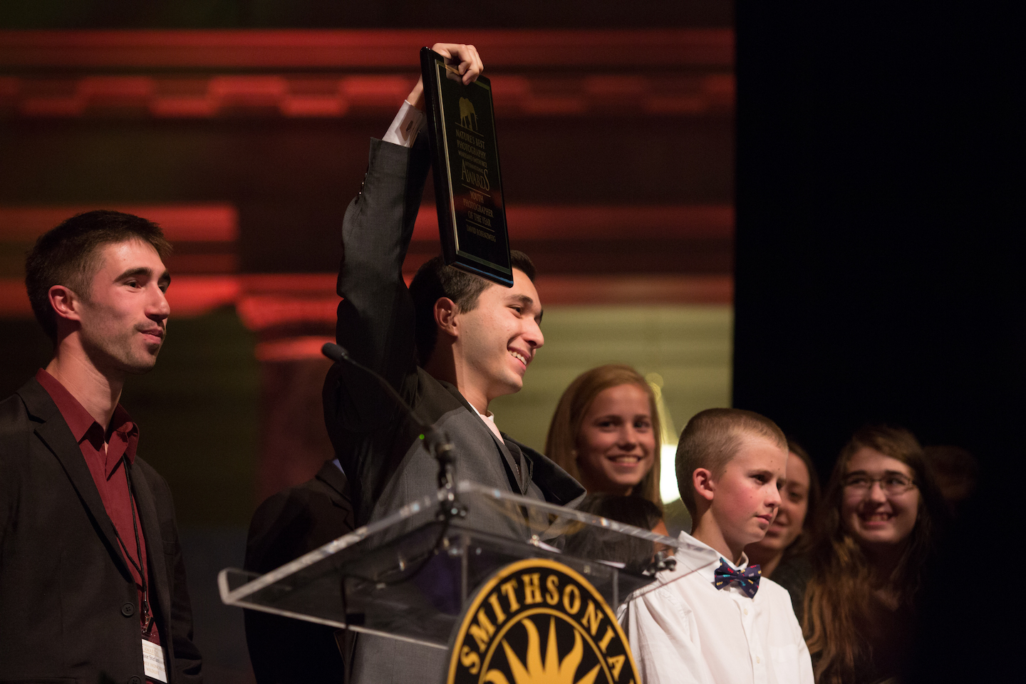 David Rosenzweig, 2016 Youth Photographer of the Year raises his award in celebration while our friends Connor Stephanison (left), Ashleigh Scully and Jenaya look on (Photo Credit: Copyright NBP Awards)
