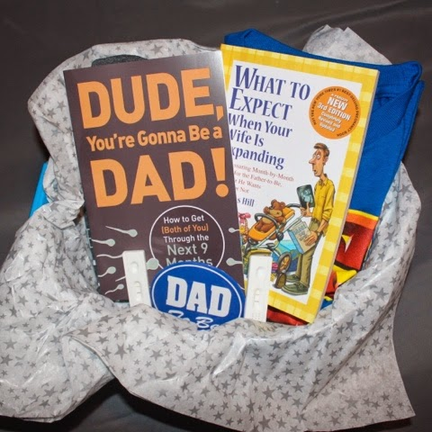 In the basket: 2 Daddy Books, 2 T-Shirts (The Man Behind The Bump & Super Dad), Dad To Be Pin & 2 Positive Pregnancy Tests.