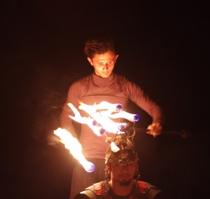Man lighting torches on another's head in the dark
