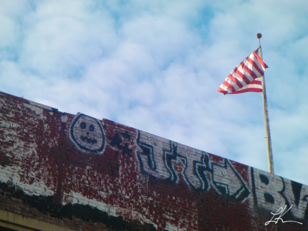 Photo of American flag above graffiti-covered wall.