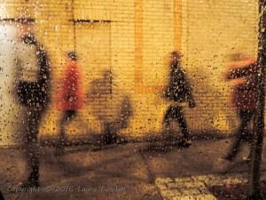 People walking on Meeting Street in the rain.