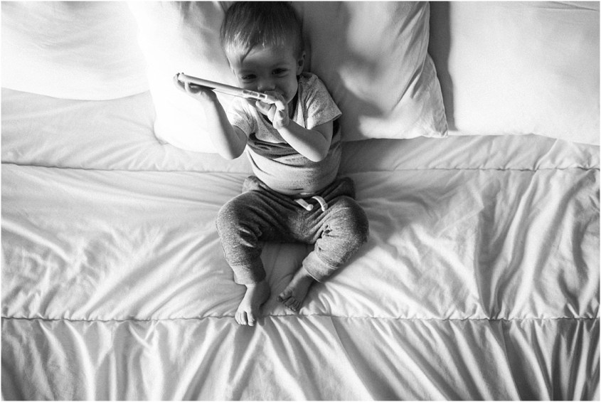 Toddler playing in bed on phone | Laura Ryan Photography