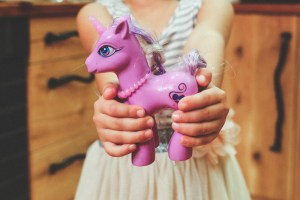 little girl holding a pink toy unicorn
