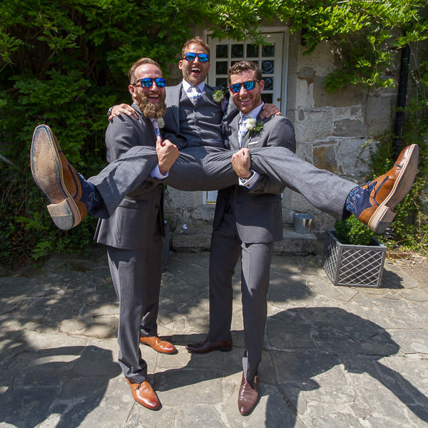 groomsmen holding the groom at Tros yr afon wedding venue