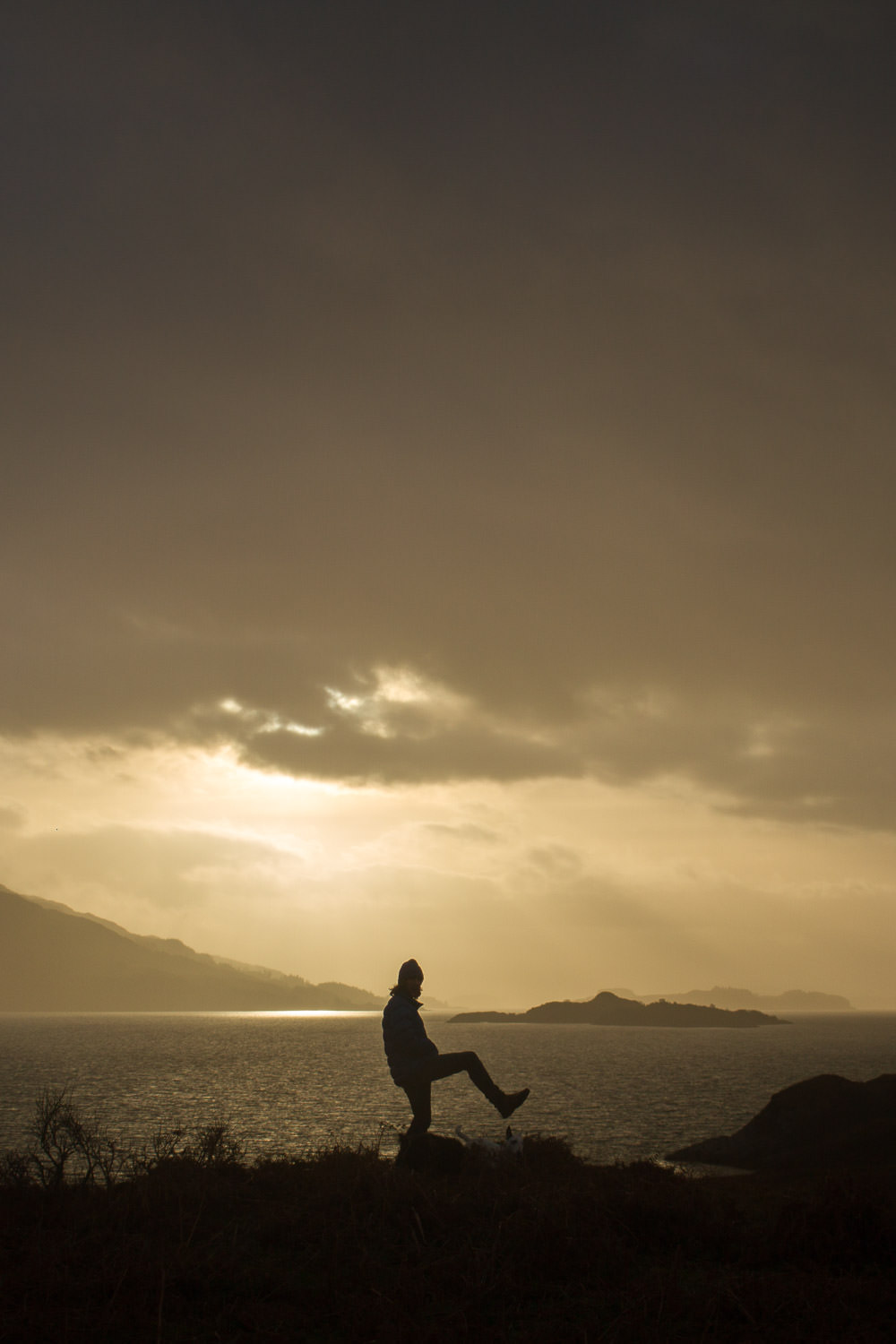 silhouette of a man infront of loch linnhe sunset