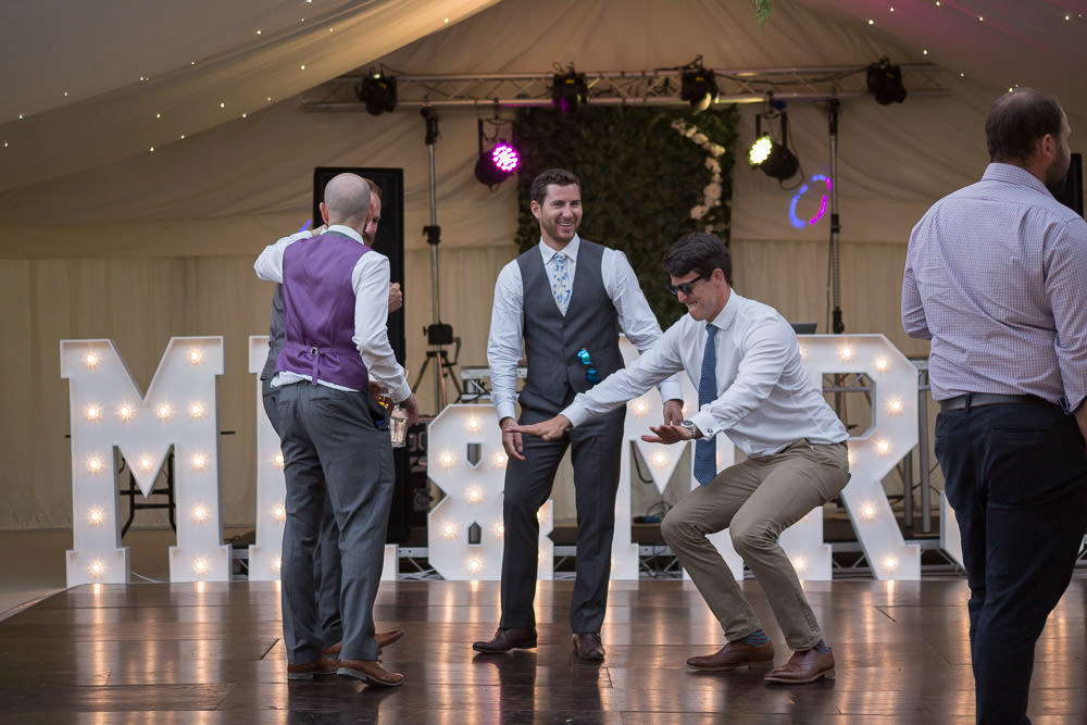 groomsmens laying down some moves on the dancefloor at Tros Yr Afon wedding venue, DIY Beaumaris castle wedding