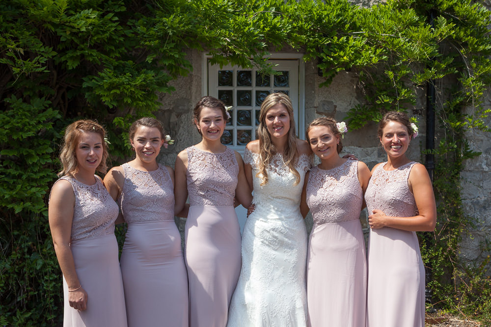Bride stands together with her bridemaids at Tros Yr Afon wedding venue, DIY Beaumaris castle wedding
