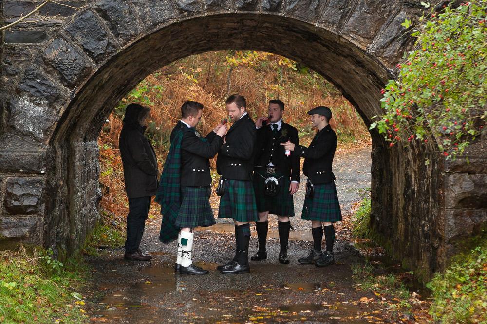 Groomsmen taking shelter from the rain at Isle of Skye Wedding