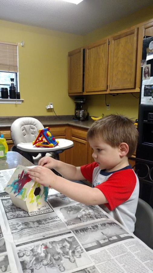 Painting a birdhouse, he looks so grown up in this picture
