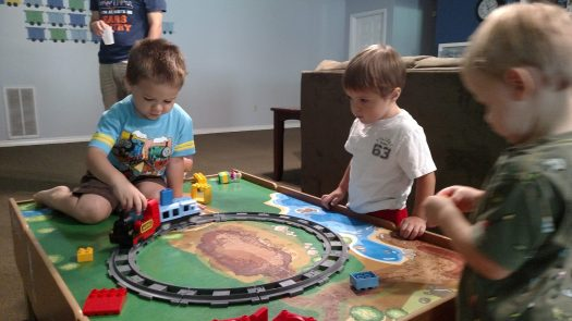 Oliver playing with his friends and his new train set
