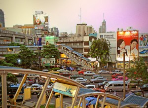 Photo: Busy, colourful scene in Bangkok. Buildings in the background, parking lot in the foreground.