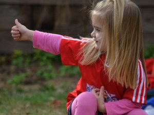 Photo of girl giving a thumbs-up to someone off-camera