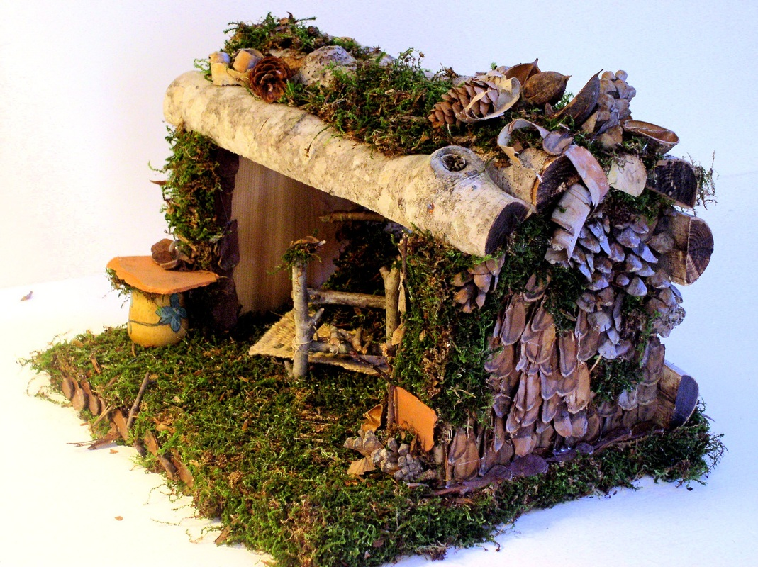 Inside the fairy house you find a handmade twig and moss bed with a burlap rug underneath, across is a twig cabinet with a birch bark top, on top of the cabinet is a clay tray.