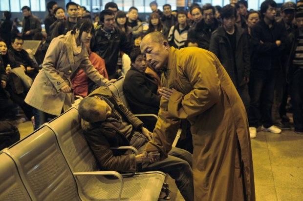 Un moine prie pour un homme subitement décédé en attendant le train à Shanxi Taiyuan en Chine
