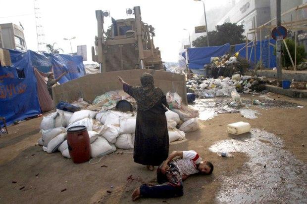 Une femme empêche un bulldozer militaire de rouler sur un homme blessé au Caire en Égypte