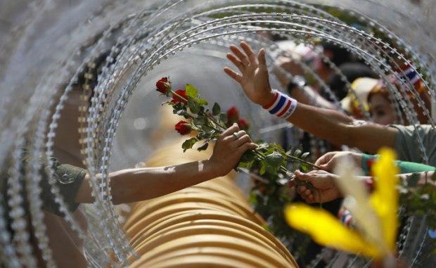 Un protestant anti-gouvernemental offre une rose à un soldat à Bangkok
