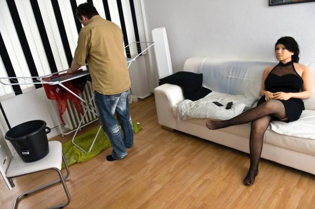 Jenny assise sur le canapé dans le salon pendant que Dirk étend son linge.