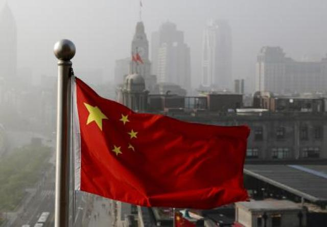FILE - In this April 14, 2016 file photo, a Chinese national flag flutters against the office buildings in Shanghai, China. Twitter locked Chinaâ#{emoji}128;#{emoji}153;s U.S. Embassy account because of a tweet in support of Chinaâ#{emoji}128;#{emoji}153;s policies on Muslims and ethnic minorities in the western Xinjiang, The tweet on Jan. 7, 2021 says Uygur women in Xinjiang have been emancipated and are no longer â#{emoji}128;#{emoji}156;baby making machines.â#{emoji}128;#{emoji}157; Twitter said it removed the tweet because it violates its policy on dehumanization. (AP Photo/Andy Wong, File)