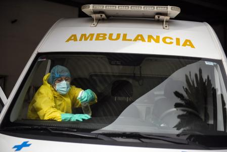 A health worker cleans an ambulance amid the new coronavirus pandemic in Montevideo, Uruguay, Thursday, April 15, 2021.(AP Photo/Matilde Campodonico)