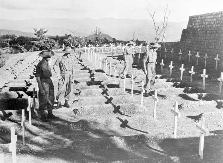 (Original Caption) Far from the White Cliffs of Dover. Kohima, Nagaland, India: Men of the Royal West Kent Regiment stand and pay silent tribute to comrades who fell in the Battle for Kohima, bridgehead to India, in the spring of 1944, when the Japs made their drive from Burma to India. For 14 days and nights of death and terror, 3, 500 British and Indian troops stood their ground here against the fury of the Jap attack. They died where they stood, but barred the road to India until relief came. November 27, 1945.
