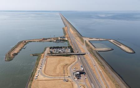 Aerial view service harbor along Dutch dike Afsluitdijk, separation between the fresh water lake IJsselmeer and the salt Wadden Se