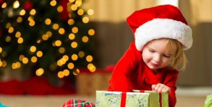 Una niña abre su regalo de navidad.