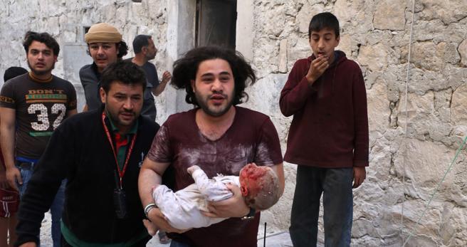 Un sirio corre con un bebe herido tras un ataque con bomas de barril en Alepo en una zona controlada por la oposición este jueves