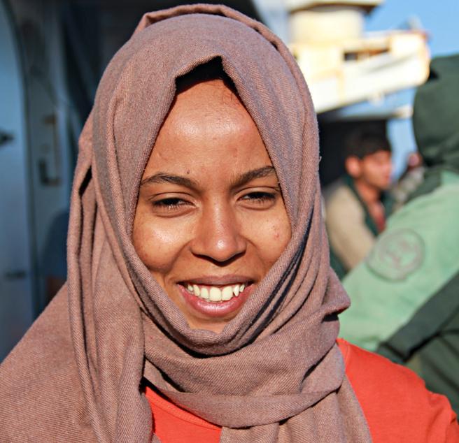 Rijala, refugiada eritrea de 23 años, sonríe camino del puerto en el 'Golfo Azzurro'