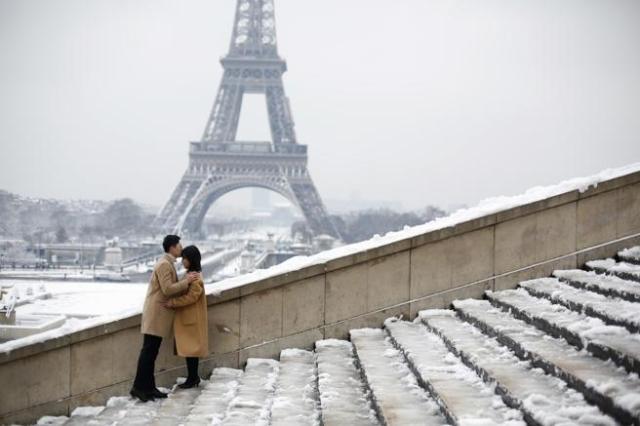 Una pareja se besa frente a la torre Eiffel en plena nevada