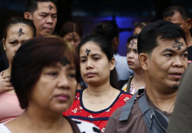 Católicos romanos de Filipinas salen de misa con marcas de ceniza en su frente