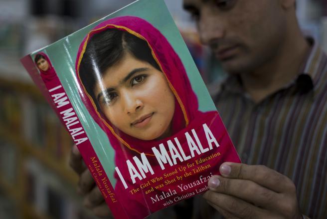 Un pakistaní lee con atención el libro escrito por la activista Malala