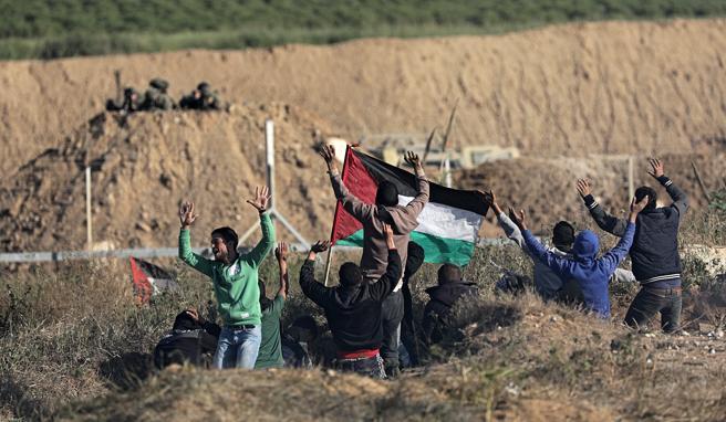 Manifestantes israelíes cerca de un control fronterizo con diversos militares israelíes, este sábado