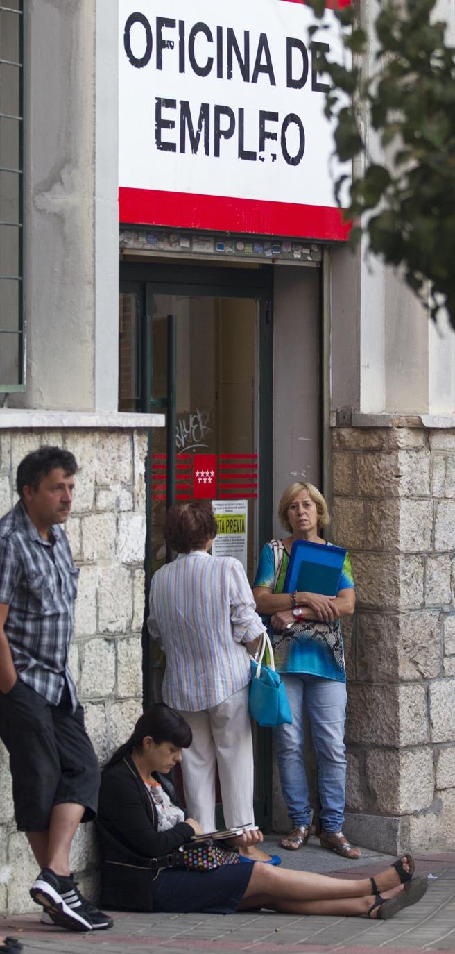 Personas esperando ante una oficina del Servicio de Empleo.