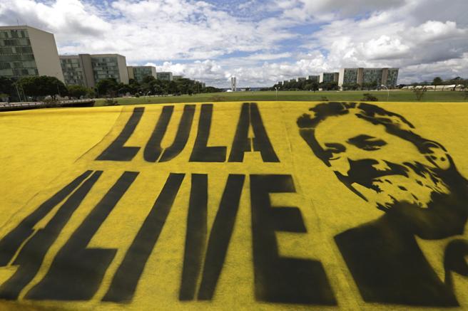 Manifestantes colocan una pancarta en apoyo al expresidente de Brasil, Luiz Inácio Lula da Silva, en el Espalanade de los Ministerios, en Brasilia