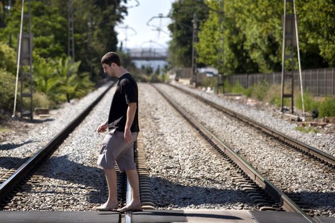 Un joven cruzando las vías del tren en Sant Feliu de Llobregat