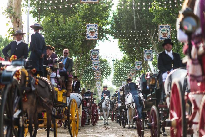 Caballos y carruajes transitan por las calles del recinto ferial de la Feria de Abril de Sevilla