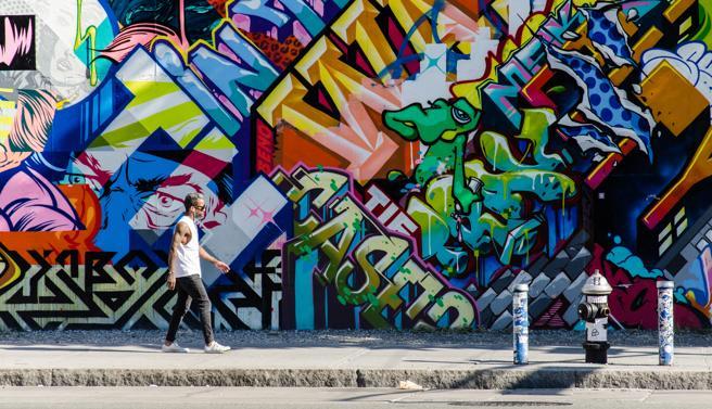 Un joven camina frente a un grafiti en Brooklyn