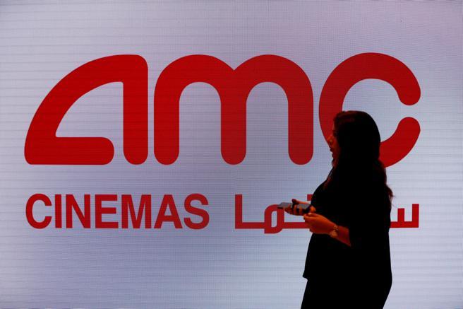 Una mujer camina frente al cartel del nuevo cine de Riad