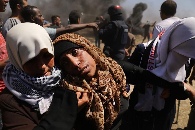 Una mujer palestina herida es atendida por dos personas en la frontera de Gaza con Israel
