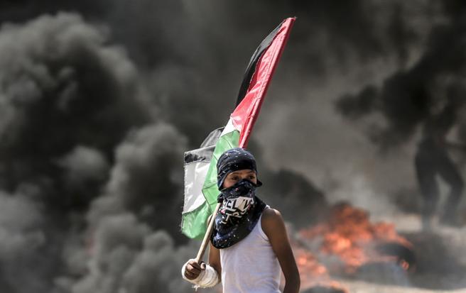 Un niño palestino lleva una bandera nacional durante los enfrentamientos entre palestinos y las tropas israelíes, en Gaza