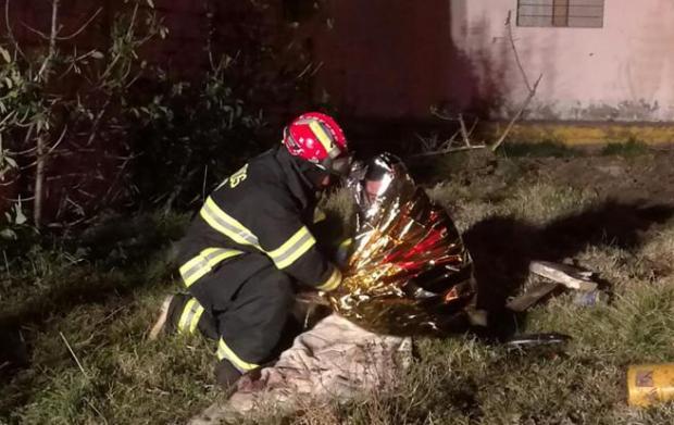 Un bombero deposita un ramo de flores junto al cuerpo de una de las víctimas