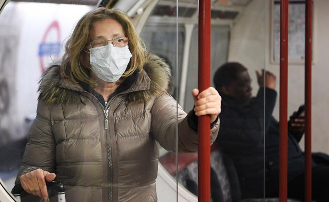 A woman wears a mask in the London underground