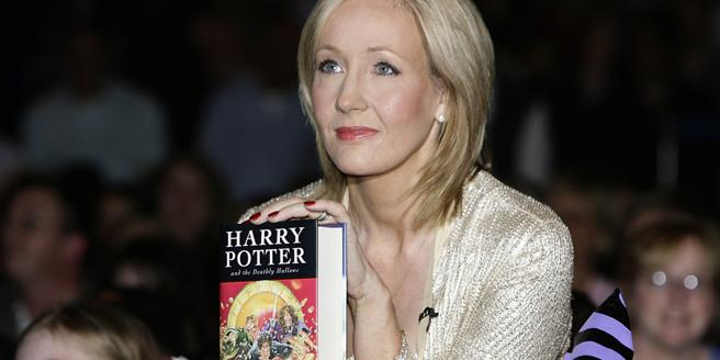 JK Rowling poses with a copy of 'Harry Potter'