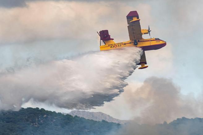 Nueve aviones y helicópteros trabajan este sábado sobre S'Albufera de Mallorca para tratar de apagar el incendio . EFE/CATI CLADERA
