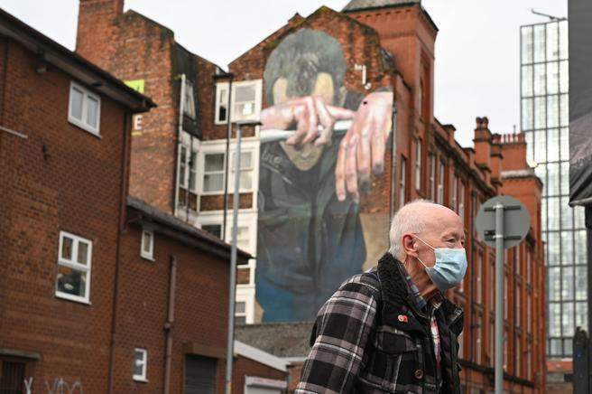 A man wearing a mask walks past a mural painted as part of the Cities of Hop festival in Manchester.