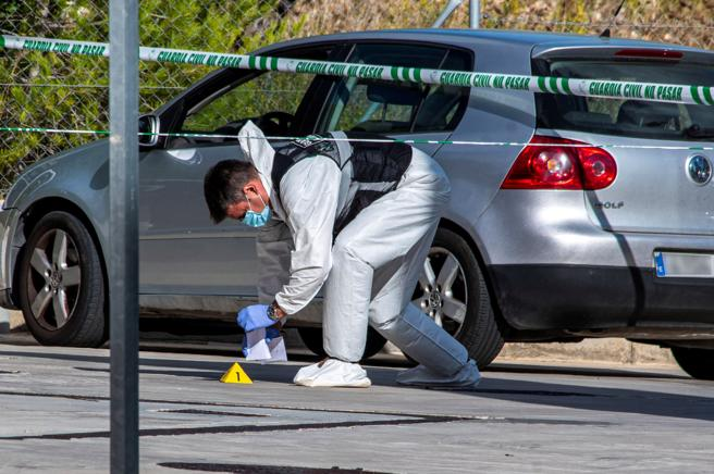 Un agente del área científica de la Guardia Civil, tomando muestras en la zona de la gasolinera donde apareció el coche con los cadáveres