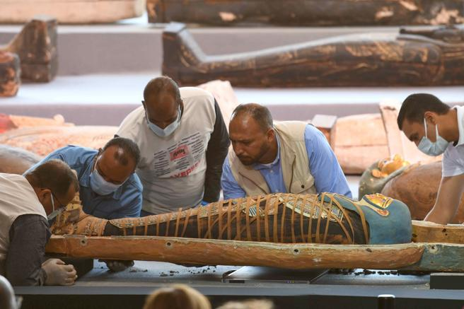Egyptian archaeologists study one of the mummies found in Sakkara