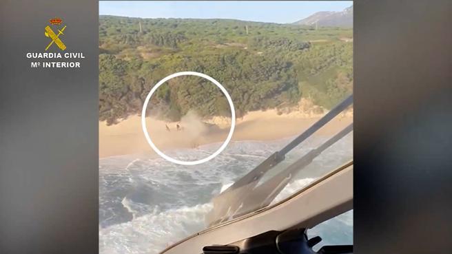 Los tripulantes de la embarcación narco, corriendo por la arena de la playa para escapar de la Guardia Civil