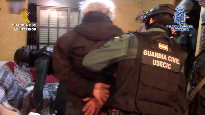 Un guardia civil conduce a uno de los detenidos mientras de completa el registro del domicilio